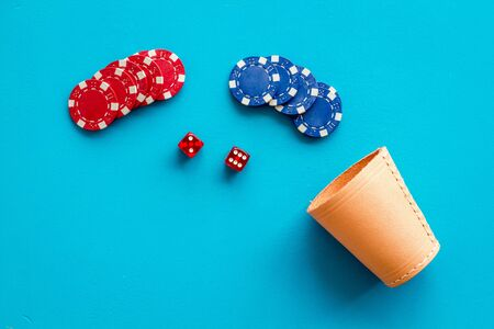 Poker hazard game concept. Chips, dices, cup for dice on blue background top-down copy space