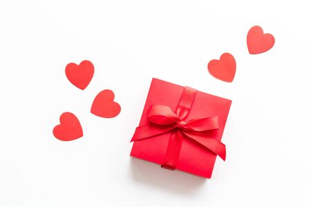 Gift to a sweetheart on Valentines Day. Red present box near hearts on white background top-down.