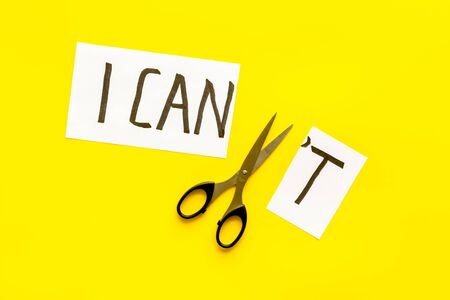 Motivation to be confident. Cut text I can't near scissors on yellow desk.