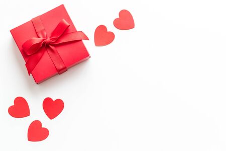 Gift to a sweetheart on Valentines Day. Red present box near hearts on white background top-down copy space