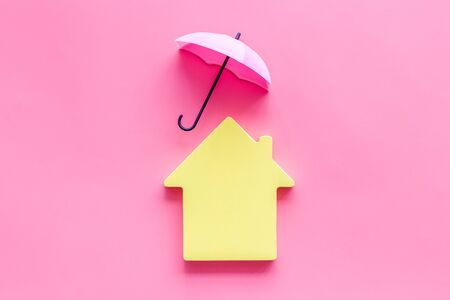 House insurance concept. Toy house defended by umbrella on pink backgound top view copy space