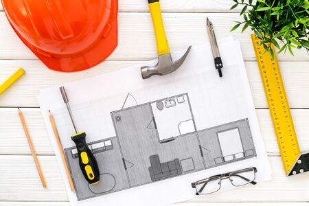 House building plan. Blueprints, instruments, helmet on white wooden background top-down.