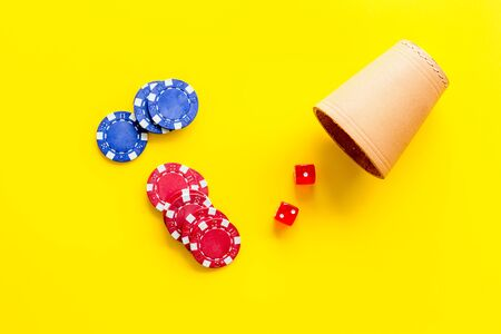 Poker hazard game concept. Chips, dices, cup for dice on yellow background top-down.