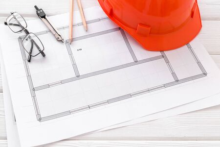 Builder helmet and blueprints on white wooden background.