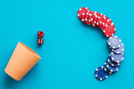Poker hazard game concept. Chips, dices, cup for dice on blue background top-down. Banque d'images