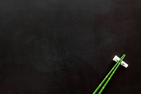 Chopsticks - green wooden utensil for sushi and rolls - on black background top-down.