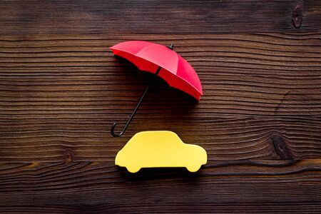 Automobile toy under umbrella on dark wooden background top-down.