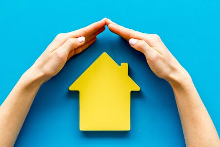 Property insurance concept. Hand defends house cutout on blue backgound top view.