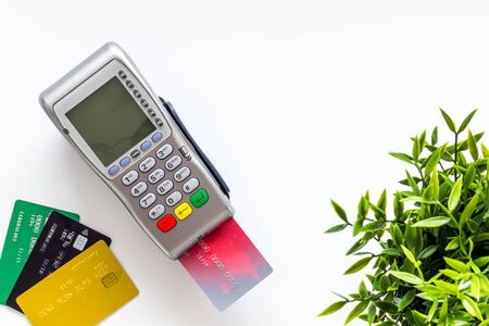 Pay by card. Plastic card inserted in terminal on white background top-down copy space