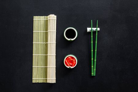 Oriental table set up. Chopsticks, ginger, soy sause, bamboo mat on black background top-down.