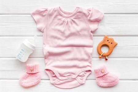 Pink bodysuit for baby girl near children's things on white wooden background top-down.
