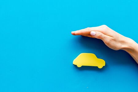 Car insurance. Hand defends automobile cutout on blue background top-down.