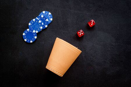 Poker hazard game concept. Chips, dices, cup for dice on black background top-down. Banque d'images
