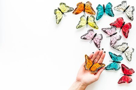 Butterfly on women hand near set of multicolored butterflies on white background top-down.