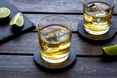 Whiskey with ice. To glasses of strong alcohol drink near lime on dark wooden background