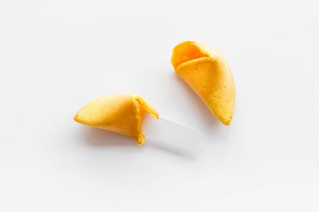 Fortune cookie - broken piece with prediction inside - on white background.