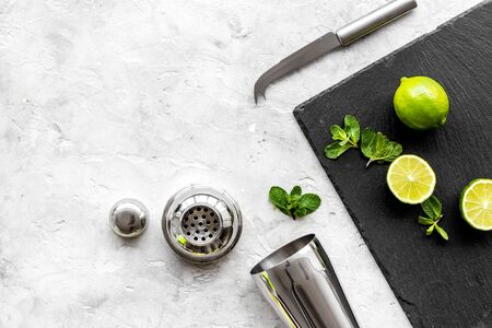 Bar background. Tools and ingredients for making cocktails. Shaker, lime on cutting board on grey background top-down.