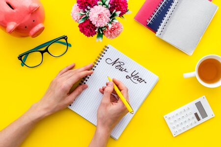 New year plans concept. Hands write goals in notebook on yellow hipster's desk top-down.