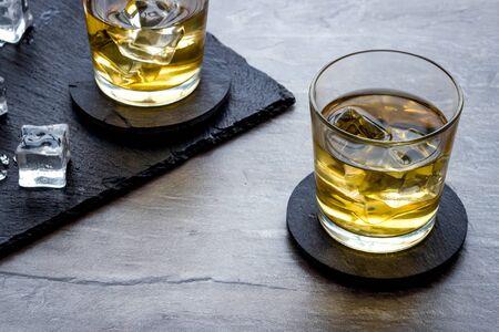 Whiskey near ice cubes on grey stone background.