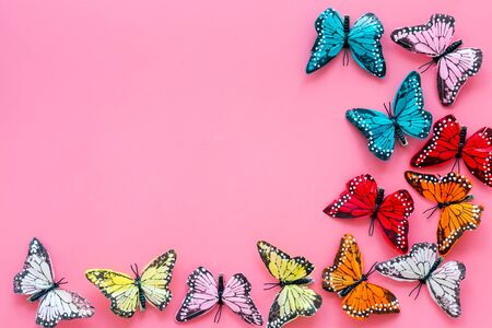 Multicolored tropical butterflies on pink background top-down frame.