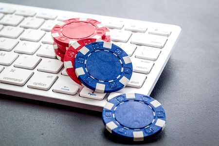 Gambling, online games. Chips near keyboard on lack background. Banque d'images