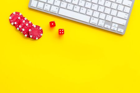 Hazard gemes online concept. Chips and dices near keyboard on yellow background top-down.