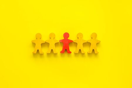 Leadership concept. People cutuots - red figure against others on yellow background top-down.