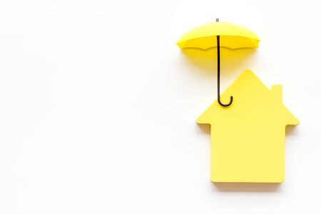 House insurance concept. Toy house defended by umbrella on white backgound top view.