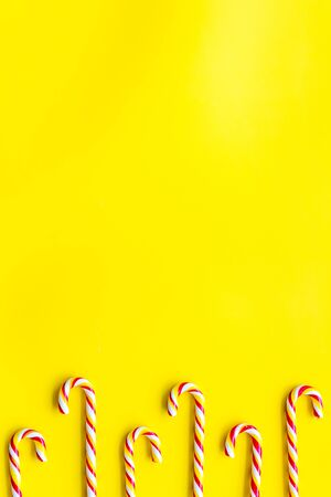 Christmas candies frame - cane with red and white stripes - on yellow background top-down copy space