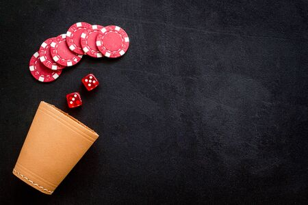 Poker hazard game concept. Chips, dices, cup for dice on black background top-down copy space