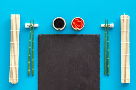 Table served for eating sushi. Chopsticks, small bowls with ginger and sause, mat on blue background top-down