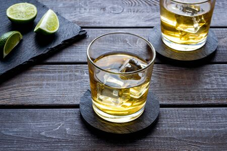 Whiskey with ice. To glasses of strong alcohol drink near lime on dark wooden background Reklamní fotografie