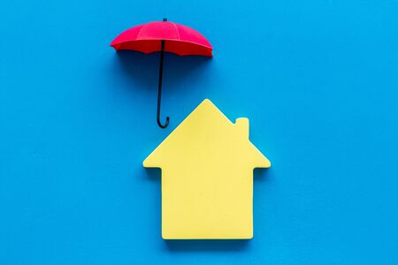 Property concept. House cutout under umbrella on blue background top view copy space