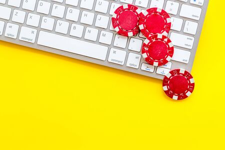 Online poker. Chips near keyboard on yellow background top-down. Banque d'images