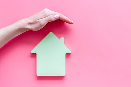 Property insurance concept. Hand defends house cutout on pink backgound top view copy space