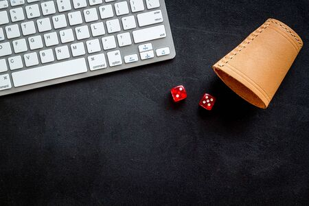 Hazard gemes online concept. Dices near keyboard on black background top-down copy space