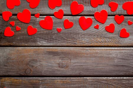 Valentines Day design. Red hearts frame on dark wooden background top-down copy space