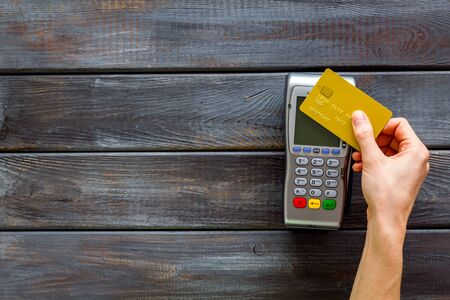 Contactless payment, paypass. Hand hold bank card near terminal on dark wooden background top-down. Stock Photo