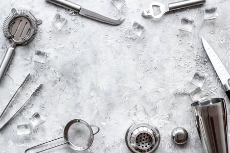 Bar utensil, tools - shaker, stainer - near ice cubes on grey background top-down.