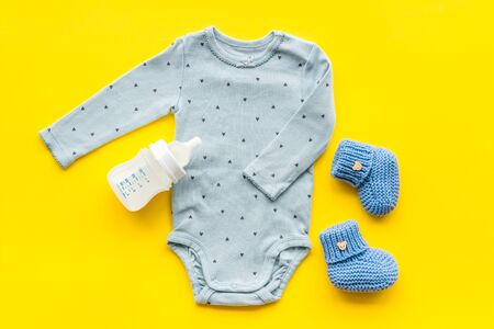 Cute baby clothes - suit - booties and accessories on yellow table top-down. Archivio Fotografico - 137880928