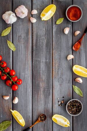 Kitchen frame with spices and food - pepper, garlic, cherry tomatoes - on dark wooden background top-down. Banco de Imagens