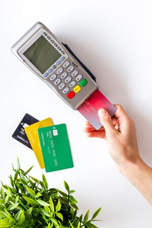 Payments in shops. Hand insert bank card in terminal on white background top-down.