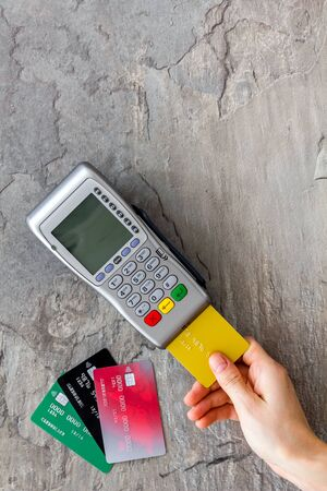 Payments in shops. Hand insert bank card in terminal on grey stone background top-down.
