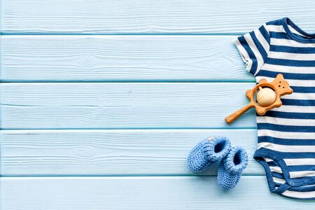 Newborn baby boy set - blue clothes as bodysuit, booties, toys - on blue wooden table top-down frame. Archivio Fotografico - 137880675