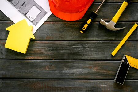 Builder work desk with hard hat, instruments and blueprints on dark wooden background top-down.