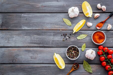 Cooking background with spices - pepper, garlic, cherry tomatoes - on dark wooden desk top-down. Banco de Imagens