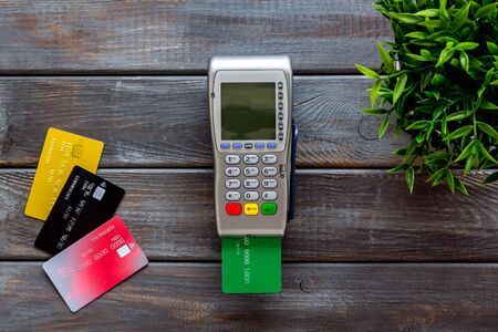 Pay by credit card in shop. Terminal and card on gdark wooden background top-down. Stock Photo
