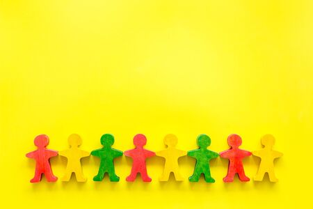 Team work, teambuilding concept. People cutouts on yellow background top-down