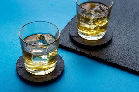 Whiskey with ice. To glasses of strong alcohol drink on blue background.
