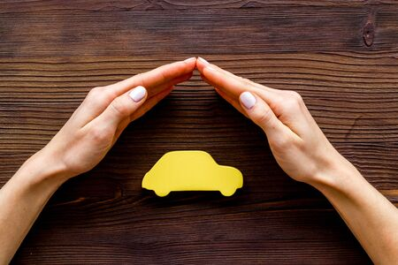 Car insurance. Hand defends automobile cutout on dark wooden background top-down.